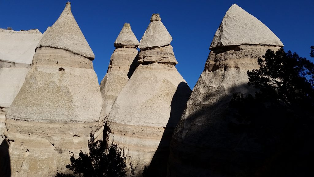 Buff-colored rocks look like 4 tipi tents standing against azure skies