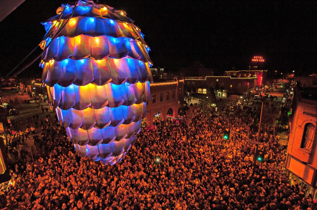 huge pinecone lit is colors hangs above crowd of thousands of people