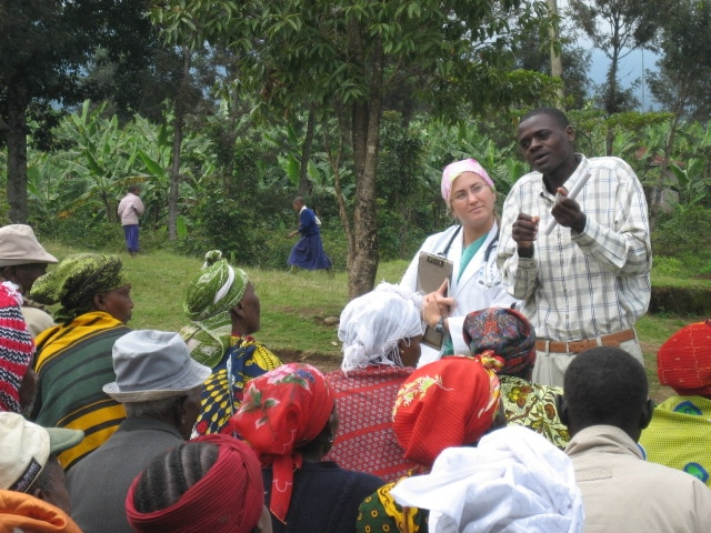 Doctor in white jacket stands next to translator and address a crowd waiting for medical services with the jungle in the background