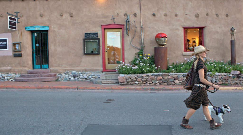 Young woman in cowboy hat walks dog on Canyon Road in Santa Fe