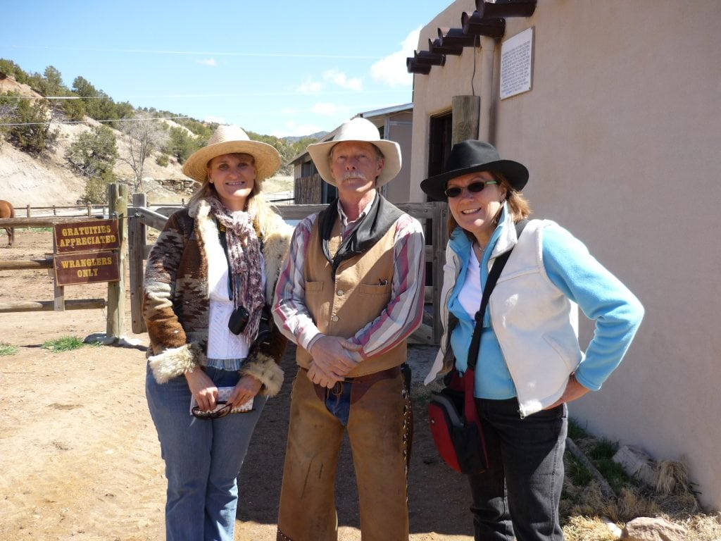 two women travel writers in cowboy hats stand next to Santa Fe cowboy trail guide