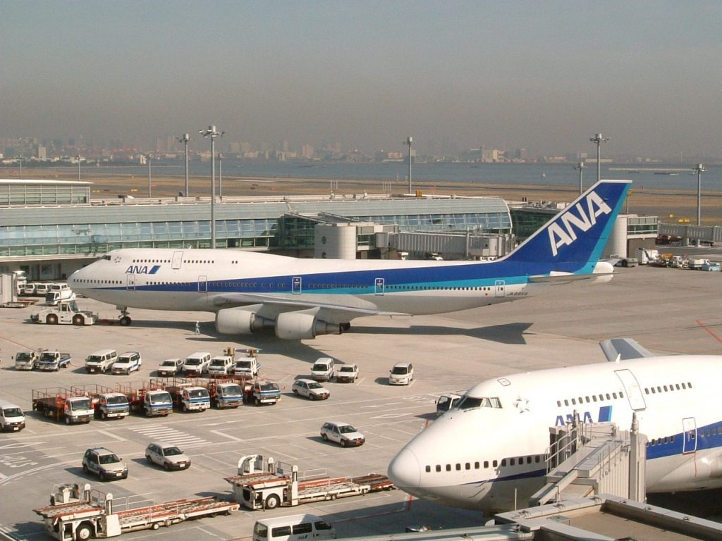 two huge airplanes at airport with body of water in background - thru the smog