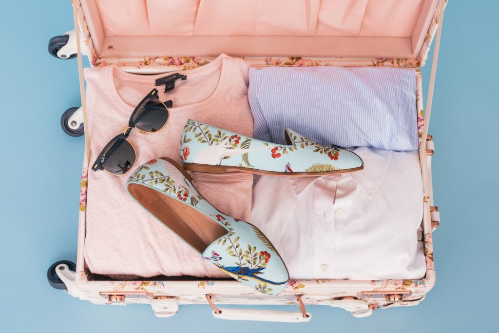 Open suitcase with sunglasses, shoes and clothing packed light