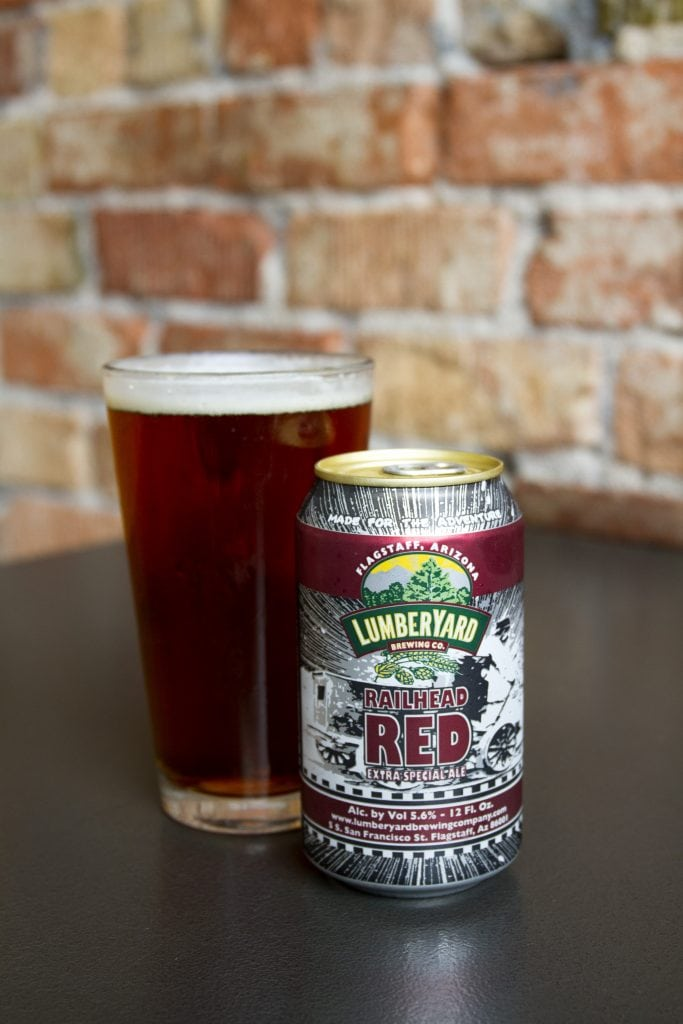 Can of Lumberyard Red Ale sits in front of pint of red-hues ale.