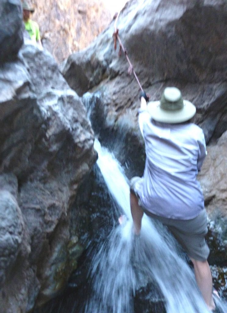 Author grasps rope to pull herself up waterfall. The water rushes over her feet and ankles.