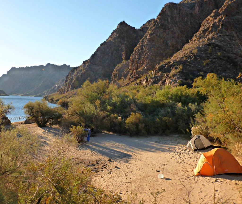 Two tents pitched on a beach of the Colorado River in the morning's bright light.