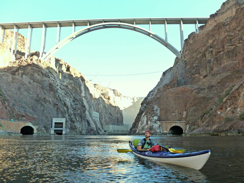 Guide Gary sits in kayak on the Colorado River with the Hoover Dam and Pat Tillman Bridge looming above