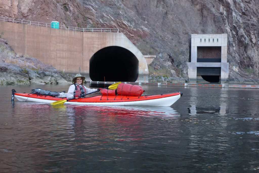 Arizona travel writer Stacey Wittig faces camera while paddling her kayak in front of a huge outlet of a spill tunnel