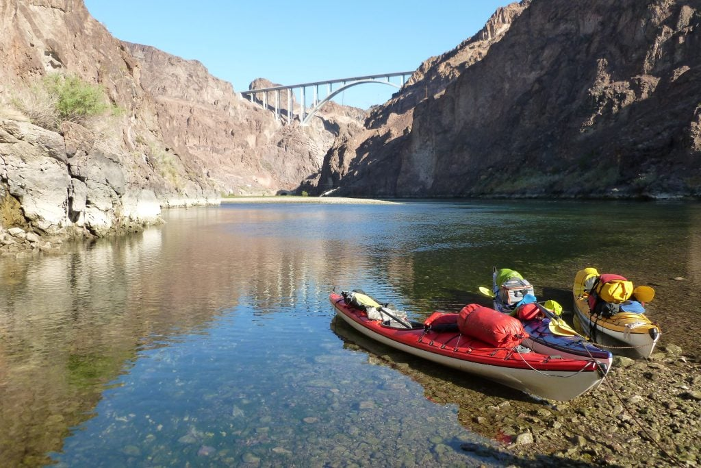Flat water of the Colorado River below Hoover DAm. Kayaks pulled onto shore loaded for the Hoover Dam kayak tour.
