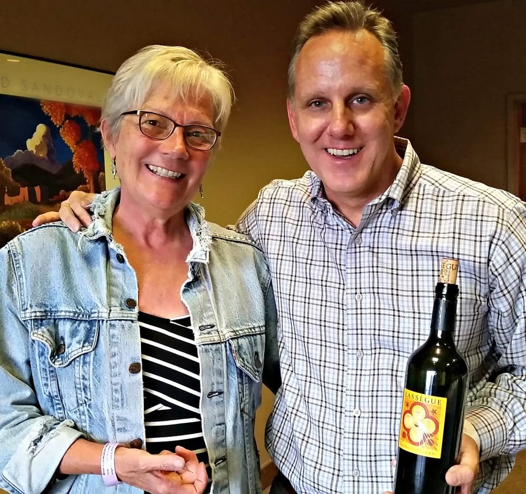 Stacey Wittig stands with Irby Woods, who is holding wine bottle