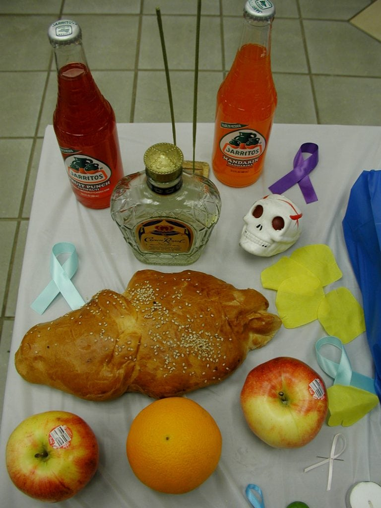 Altar with food offerings including apples, Crown Royal whiskey and Day of the Dead bread