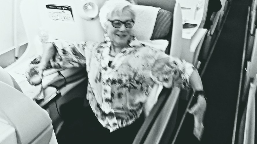 Unstoppable Stacey in Business Class seat with arms spread to show how much room she has in the width of her China Southern seat.