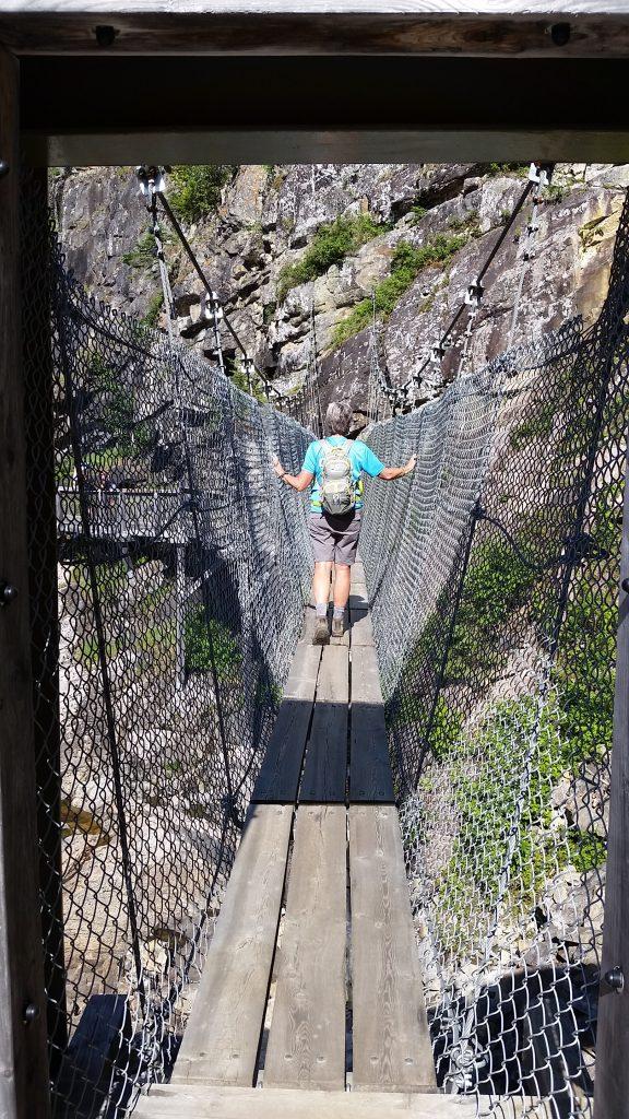 Blogger Stacey Wittig walks on swinging suspension bridge at Parc de la Caverne Trou de la Feé