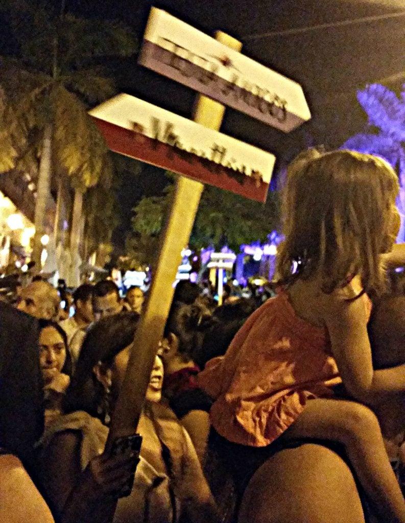 sign reading Fiesta Amigos leads the Dia de los Muertos procession