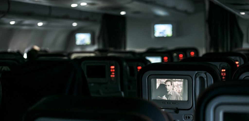Interior of dark jumbo jet with a few in-seat monitors playing movies during overnight flight