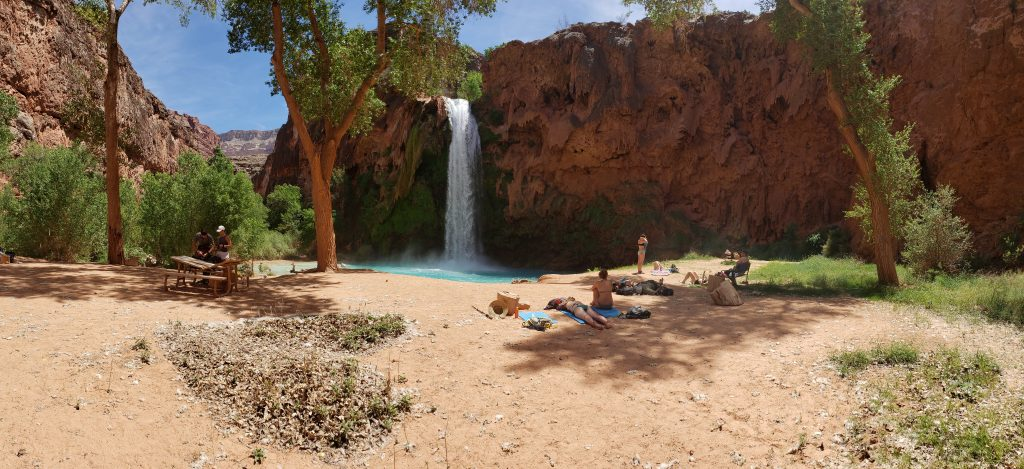 People enjoying sand beach in front of Havasupai Falls