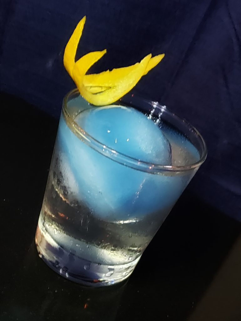 cocktail with blue ice ball on black background