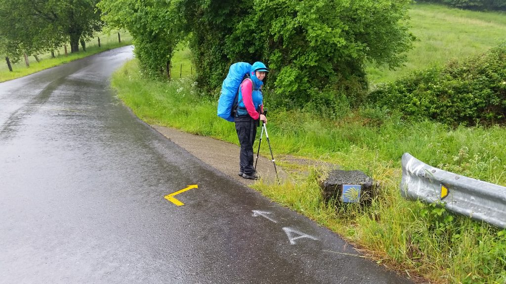 Woman in best backpacking rain jacket with high collar and hood stands in the rain next to a Camino de Santiago trail marker