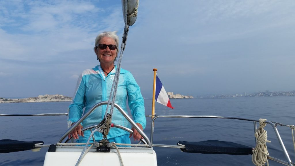 Unstoppable Stacey stands at wheel of sailboat with French flag and island in the background