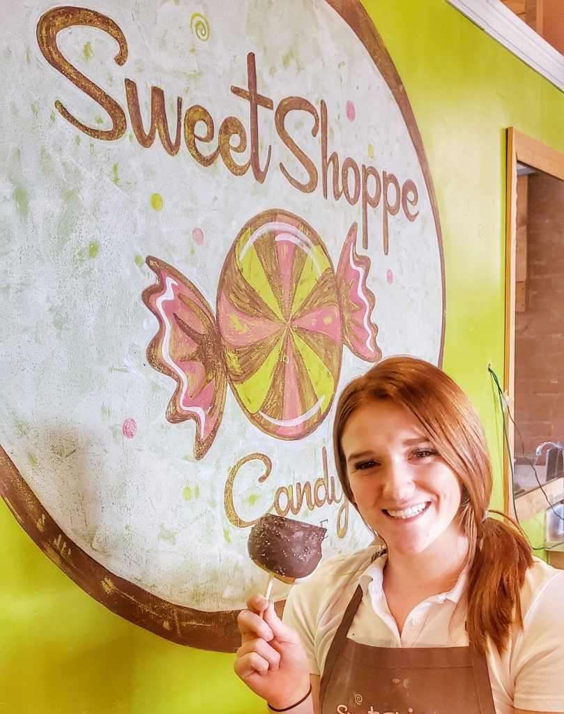 Young woman holding candy apple in front of green wall and sign
