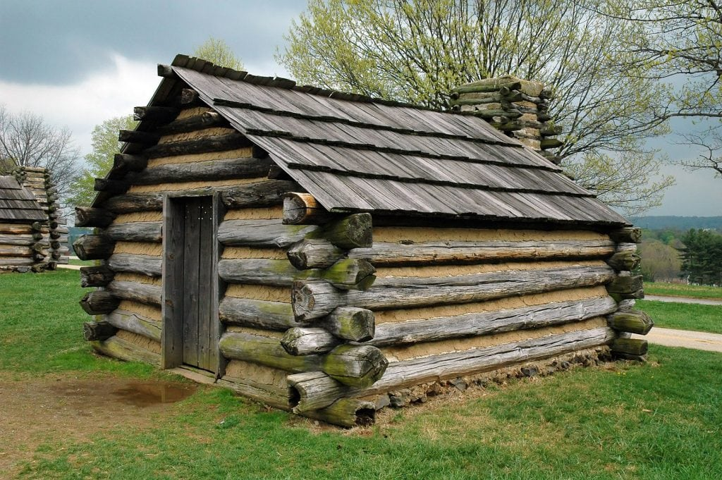 replica of log cabin showing logs alternated with lareg end, then narrow end of logs