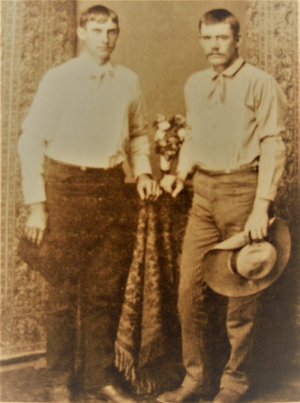 Studio shot of two young men standing in cowboy boots with cowboy hats in hands.