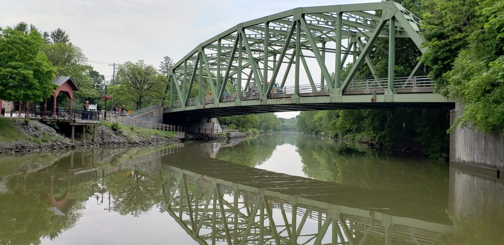 Industrial train bridge and reflection over serene canal waters