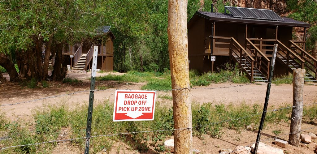 Sign on pack mule paddock reading 'Baggage Drop Off Pick Up Zone