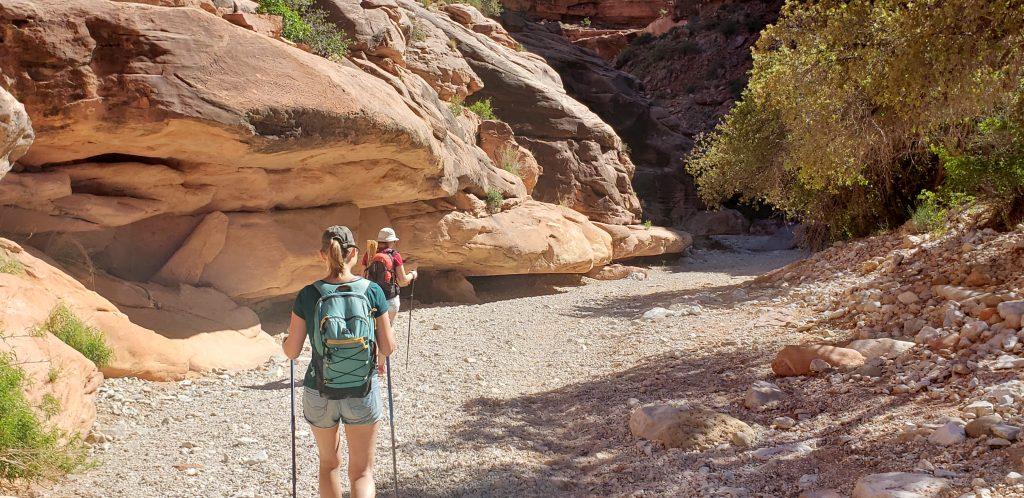 Two women hike into narrow canyon toward Havasu FAlls on the Havasupai Reservation
