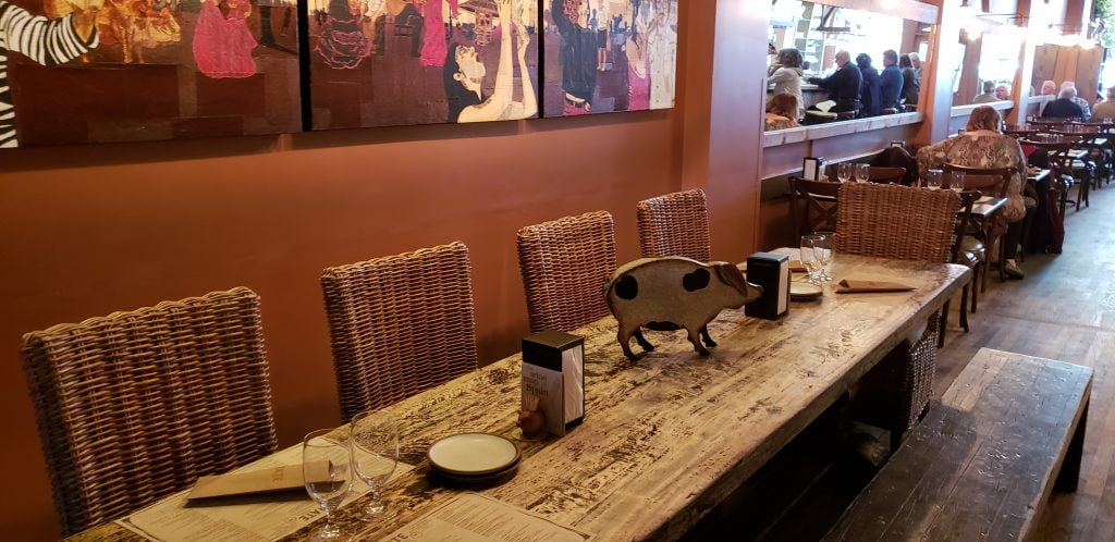 Long rustic table with wood cut out pig as centerpiece of Spanish themed Curate restaurant