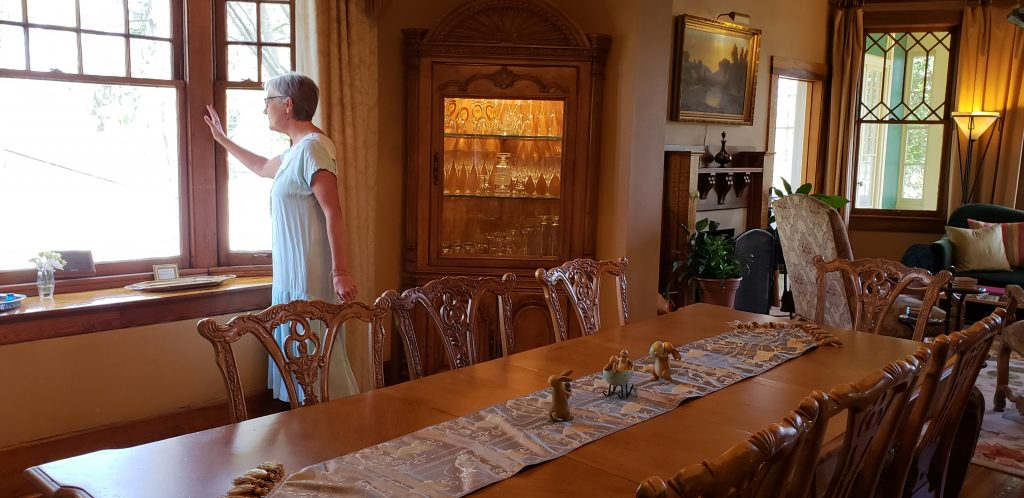 Long dining table in spacious Cumberland Falls Bed and Breakfast dining room with author standing near large windows