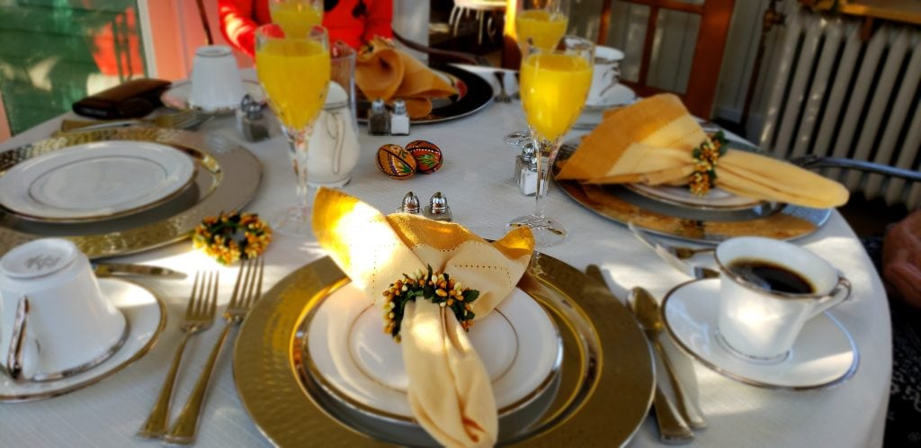 Table set with gold chargers and fancy table linens make you feel like a Vanderbilt