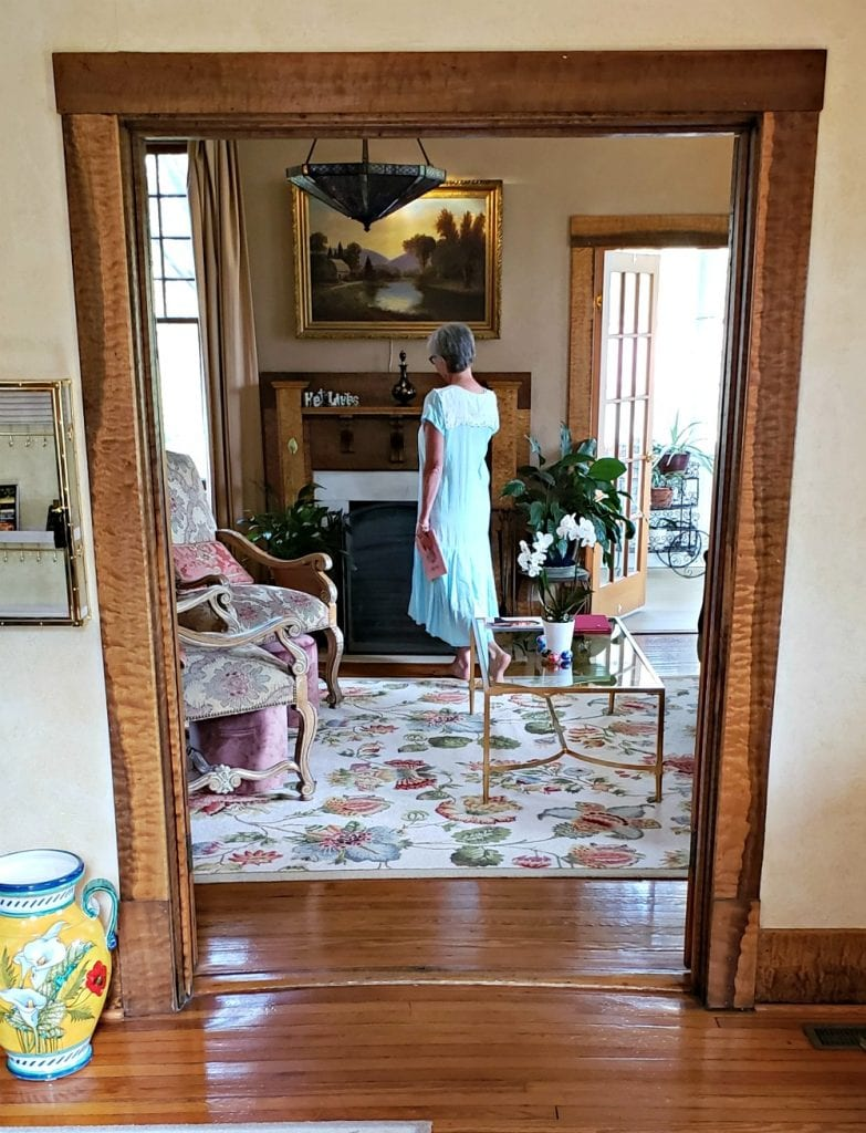 Doorway to parlor frames author standing by fireplace at one of Asheville NC B&Bs