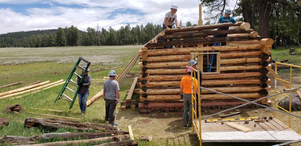 Volunteers in construction helmets work on small Brolliar log cabin