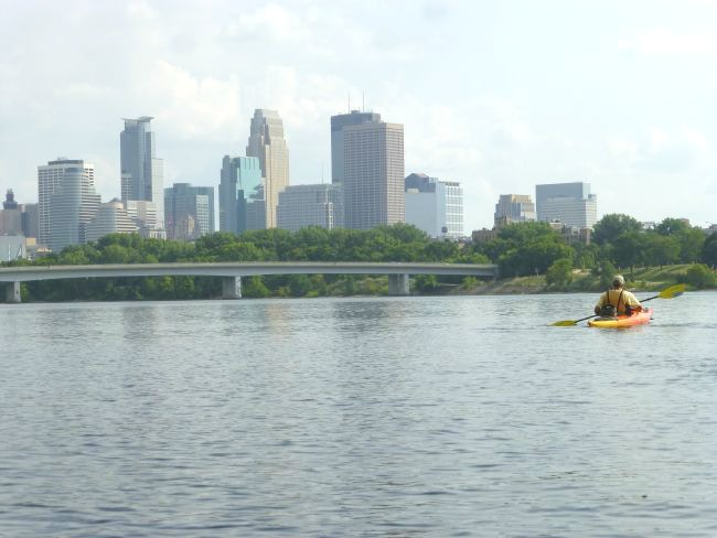 Kayaker on Mississippi River with Minneapolis Skyline in background during kayak tours in Minneapolis