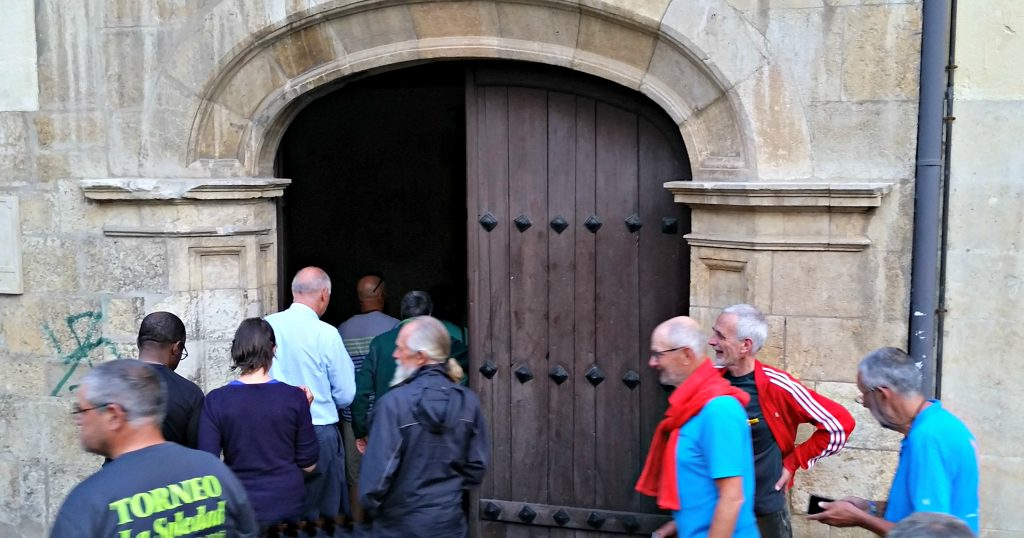 Groups of pilgrims enter the double door of the chapel at Monasterio de Benedictinas Santa María de Carbajal León. A stone arch is over the doors.