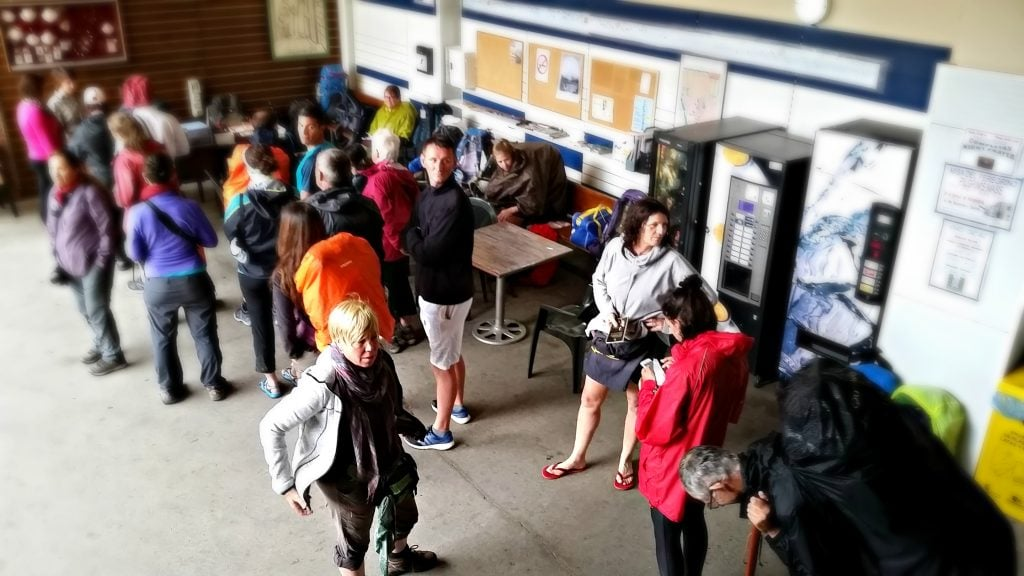 Wet and weary pilgrims stand in line at the registration desk of the Benedictine monastery.