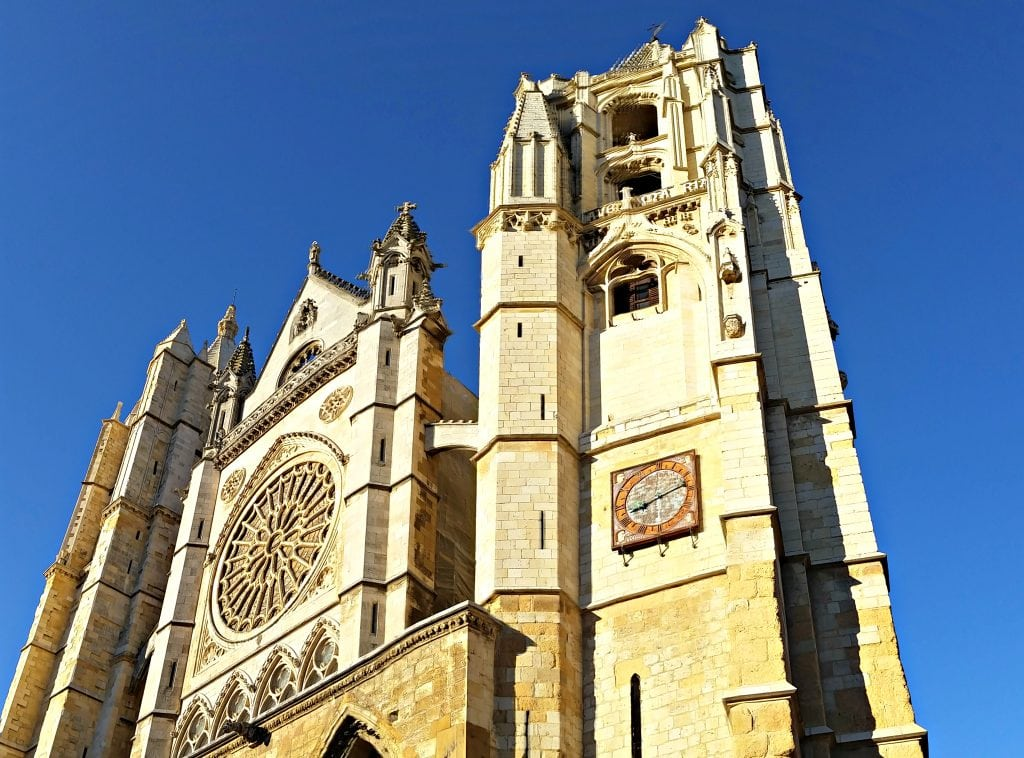 The tall Leon Cathedral made of creamy yellow limestone is framed by azure blue skies on the Camino de Santiago.