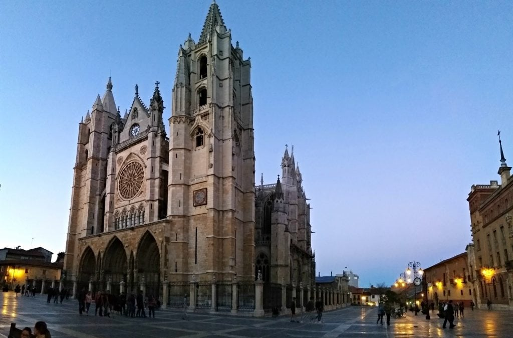 The León Cathedral at dusk with street lights glowing in the plaza