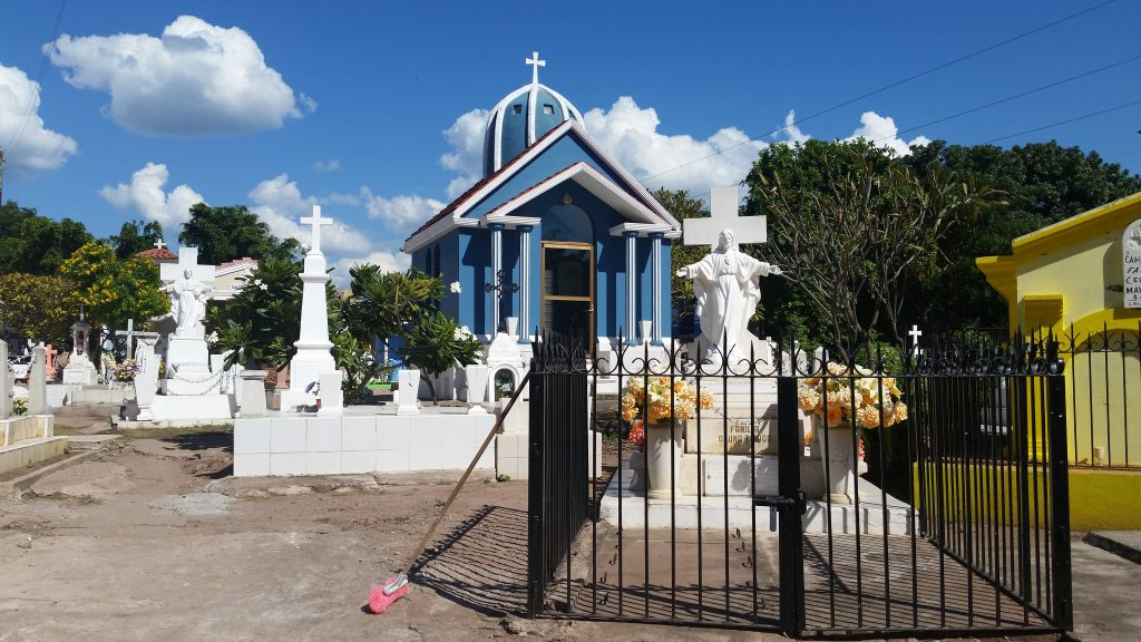 Cemetary with bright blue mausoleum and white crosses.