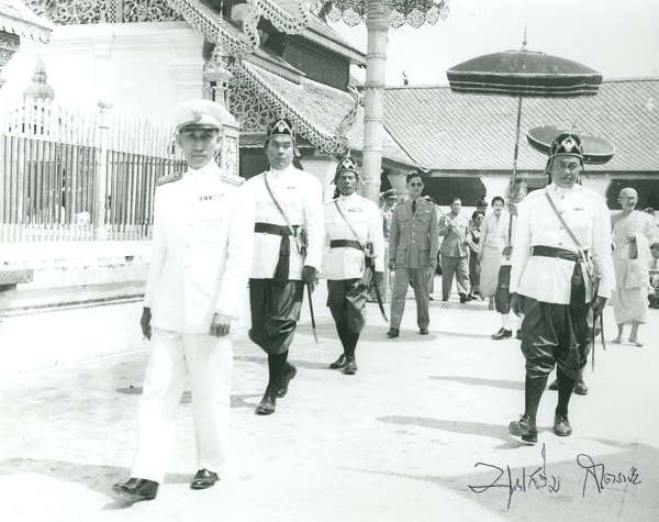 1958 black and white photo of King Rama IX in walking processional with attendants dressed in traditional Thai regalia.