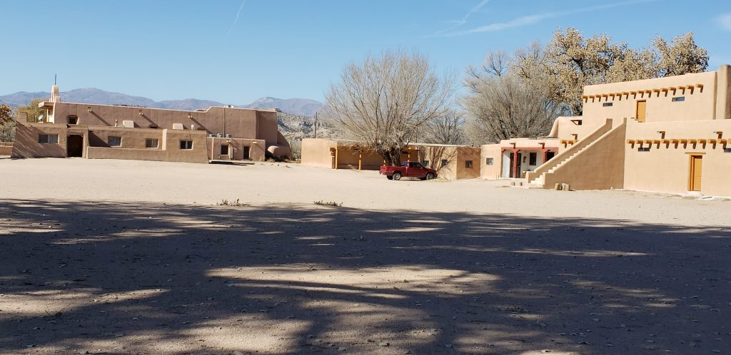 Large plaza in foreground withtwo-story pueblo buildings of adobe surrounding.