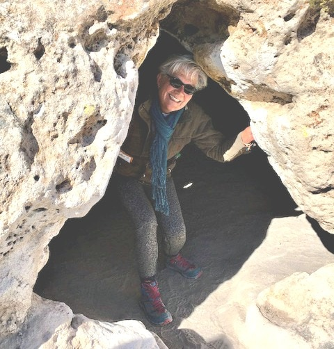 Stacey peeks out from dark hollow in the light colored cliff face,