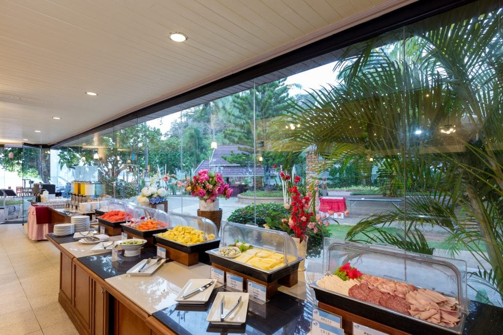 six displays of food are lined near a floor to ceiling glass window.