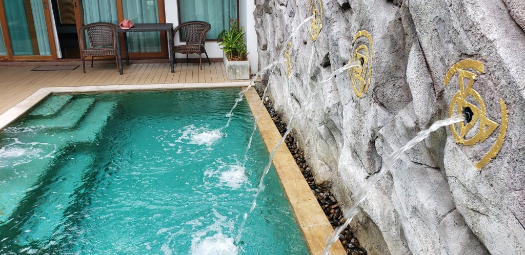 Small swimming pool with four water falls spewing water from rock wall.