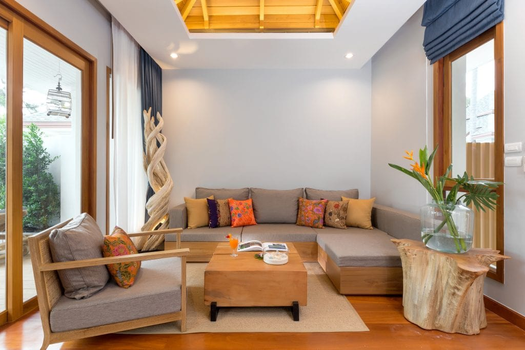 Couch with colorful pillows, upholstered chair with wooden arms, wooden coffee table and area rug in Krabi Resort villa.