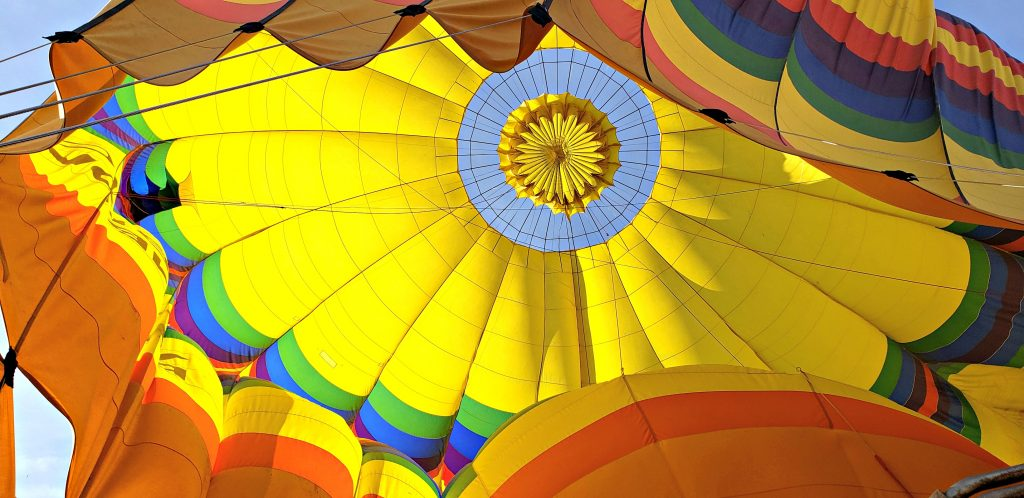 Colorful deflating balloon looking up at its center - blue sky shows through