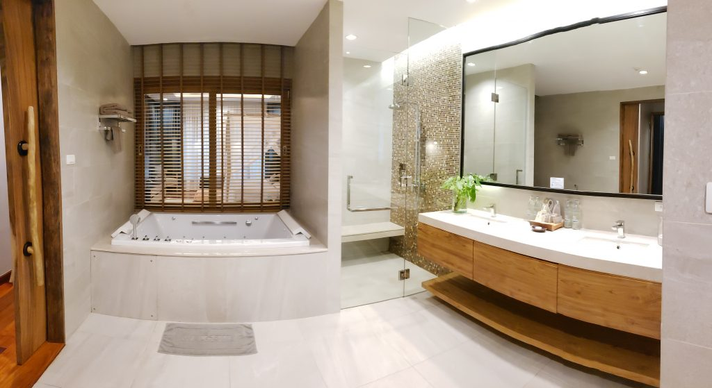 Bath room with white tiled walls and floor, contemporary wood counter with white sinks and Jacuzzi tub.