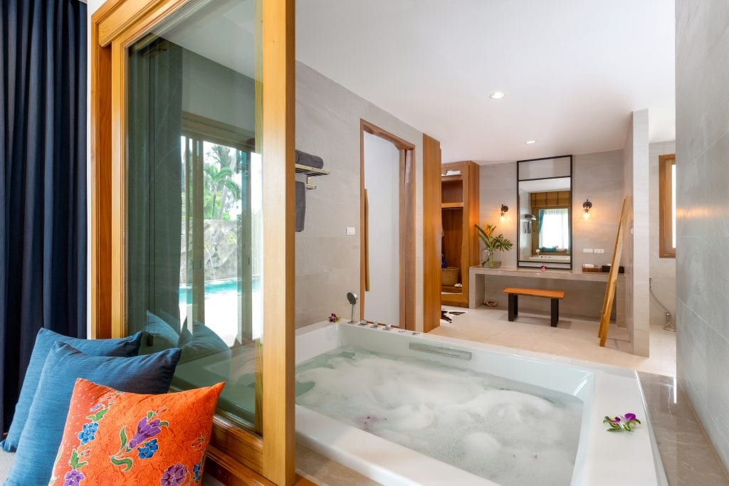 White Jacuzzi tub bubbling with water and sliding window open to see bath area.
