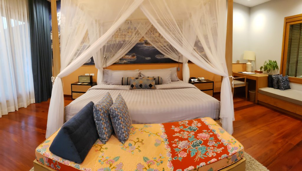 Bed from foot of bed looking through white canopy to wooden headboard and colorful pillows.